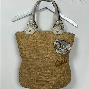 Coach straw bag with white flower on the front.